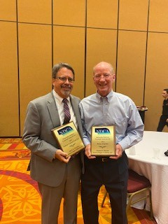 Mark Novotny and Daniel Chesire pose with award plaques